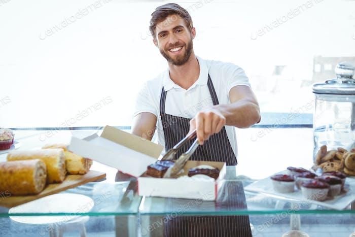 Smiling worker prepares orders at the bakery