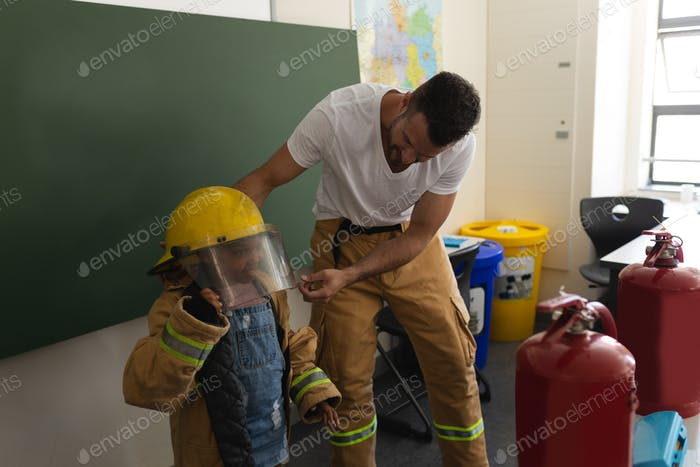 Male firefighter help to wearing fire uniform to a schoolgirl in classroom of elementary school