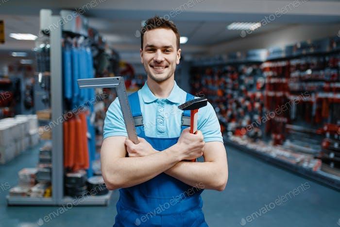 Arbeiter hält Hammer und Ecke im Werkzeugladen