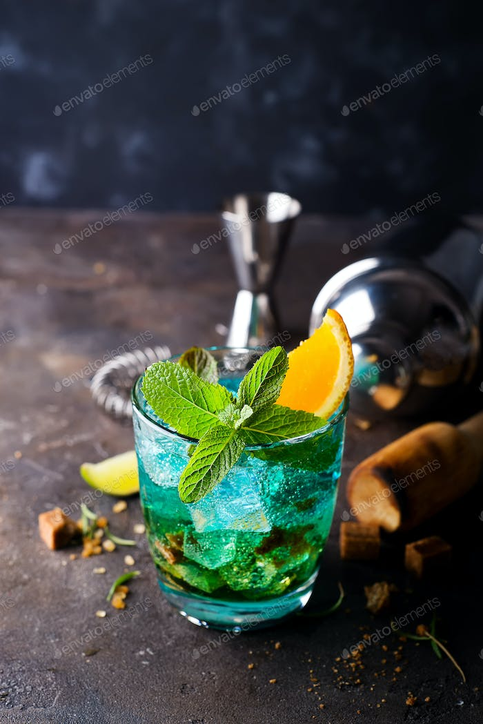 Alcoholic cocktail with sambuca, liqueur, orange juice, crushed ice and mint