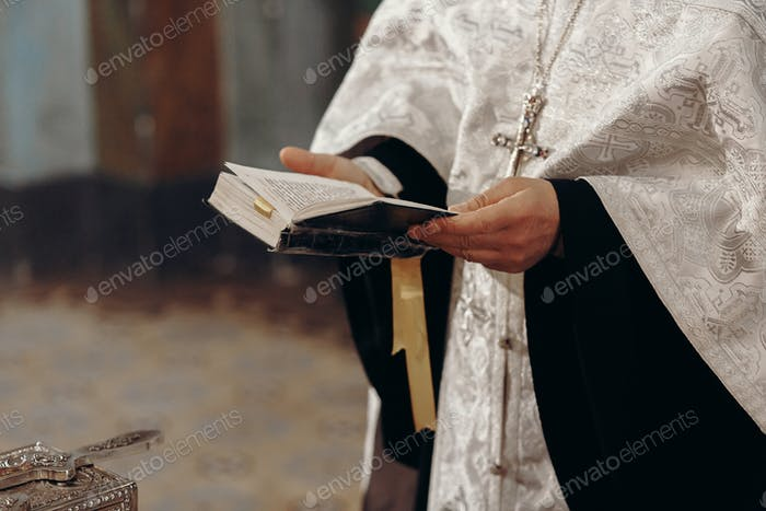 Priest reading holy bible in christian church during orthodox wedding ceremony