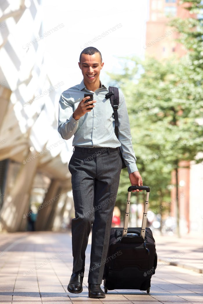 Full body traveling businessman walking in city with suitcase and mobile phone