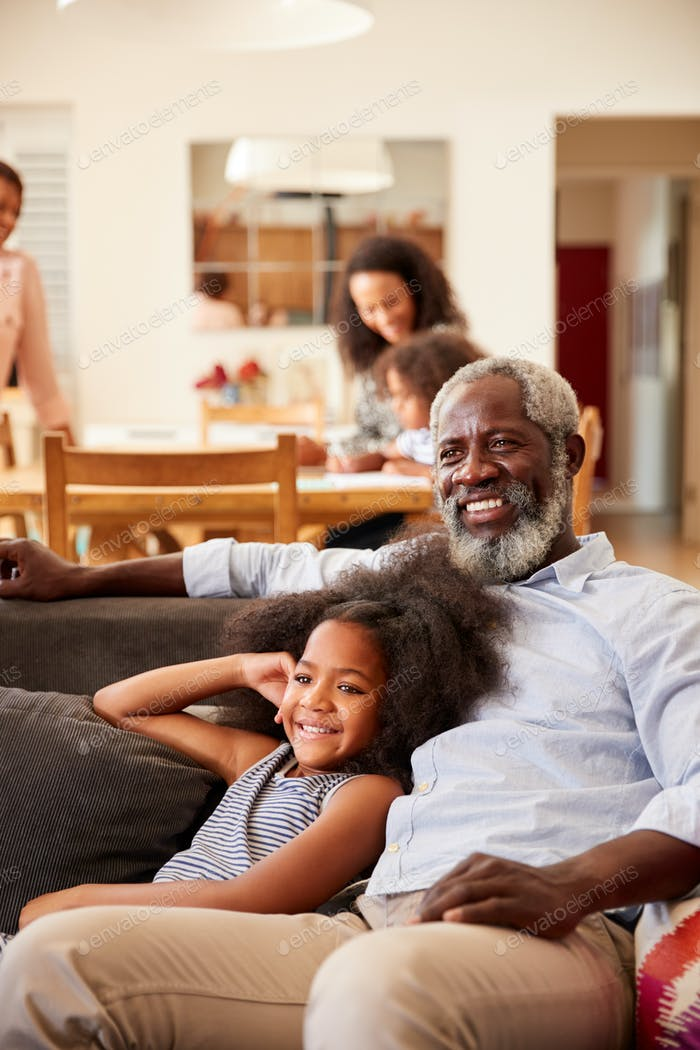 Grandfather With Granddaughter Sitting On Sofa At Home Watching Movie With Family In Background