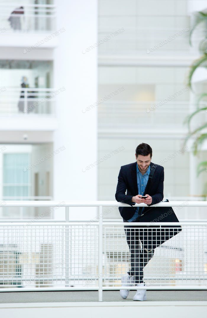 Businessman sending text message on mobile phone