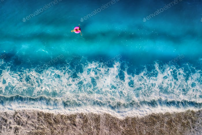 Aerial view of young woman swimming on the pink swim ring in the