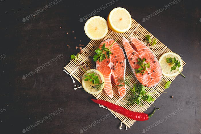 Salmon steaks with lemon and spices on black background with copy space text.