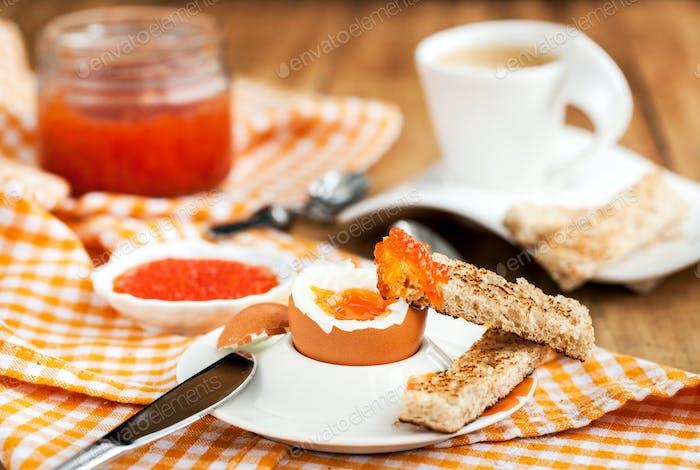 Gekochtes Ei mit rotem Kaviar, Toast und Kaffee