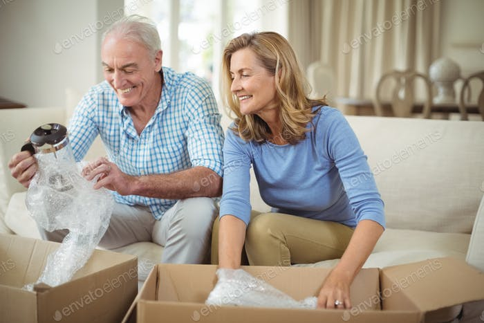Senior couple unpacking carton boxes in living room