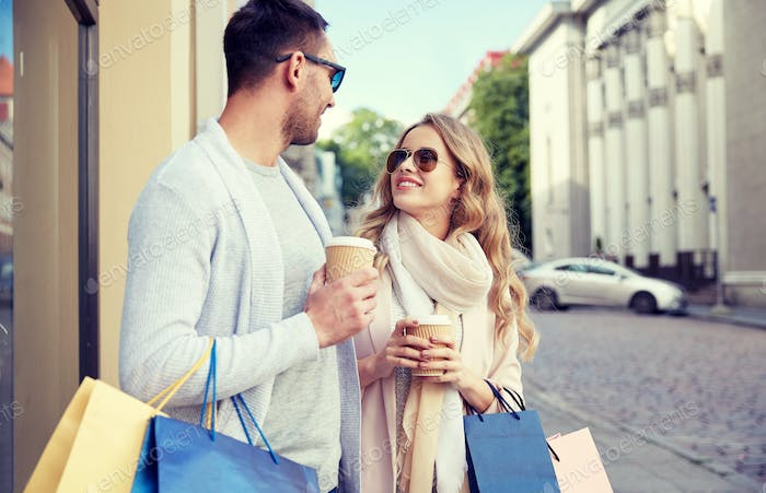 happy couple with shopping bags and coffee in city