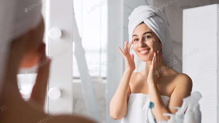 Woman Applying Eye Cream Taking Care Of Skin In Bathroom
