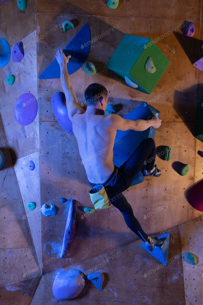 Unrecognizable boulderer on climbing wall