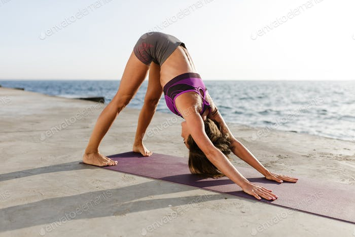 Young woman with dark short hair standing and leaning on her hands training yoga poses by the sea