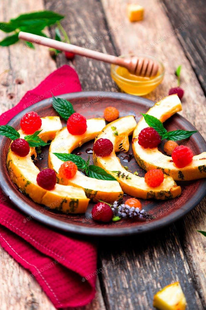 Grilled pumpkin with honey, raspberry and mint on wooden rustic background. Close up.