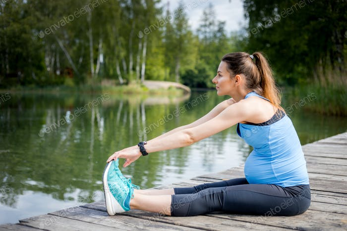 Pregnancy exercise, pregnant woman stretching outdoor