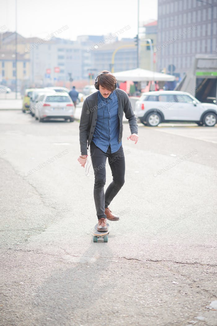 Young handsome caucasian man with mustache skating through the s