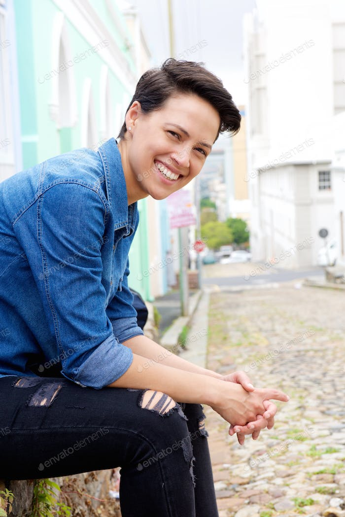 Smiling young woman with short hair sitting outside