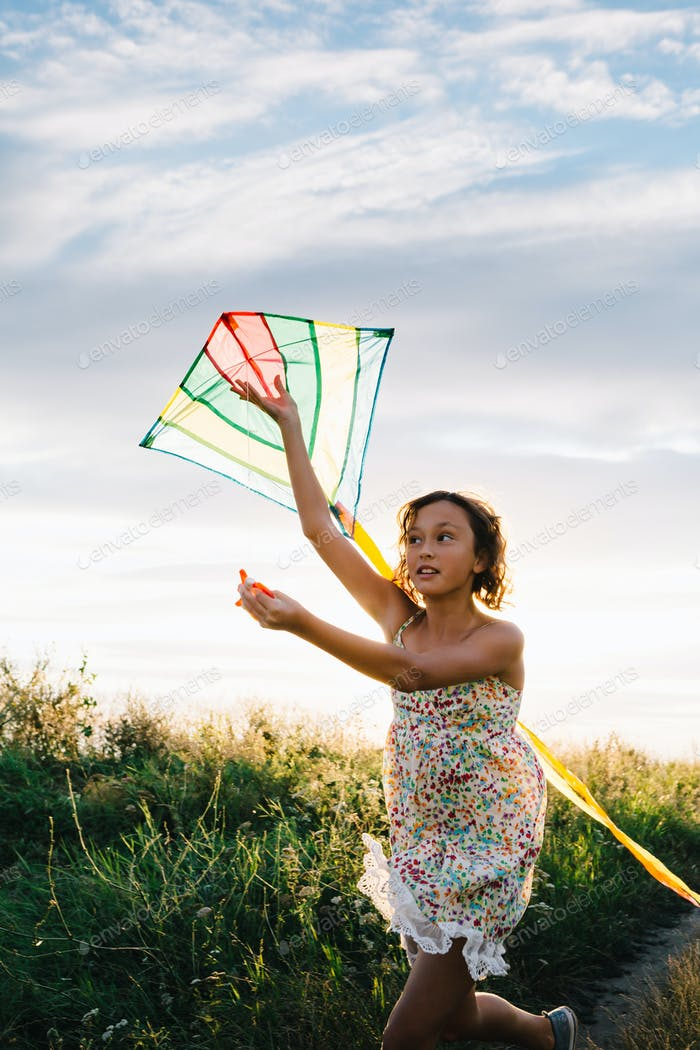 Girl holding kite and running in field