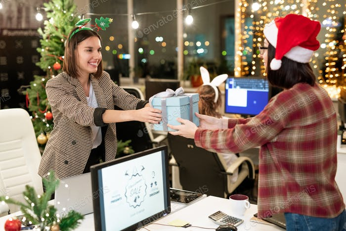 Two happy young businesswomen giving presents to each other on Christmas day