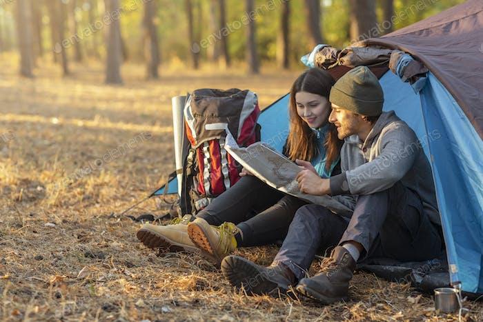 Romantisches Paar Camping im Freien, sitzen im Zelt und Karte überprüfen