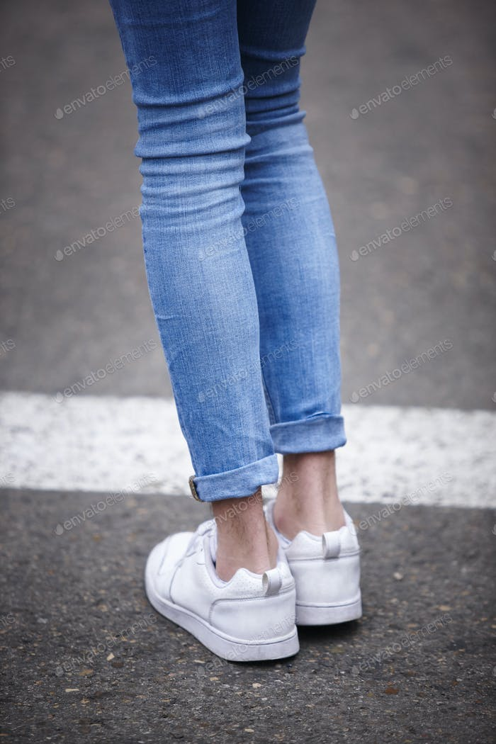 Male legs with jeans and sneakers. Hipster trendy people. Vertical