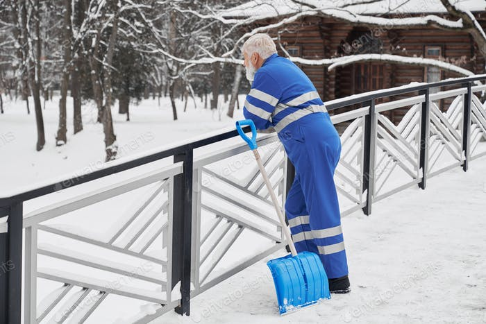 Janitor leaning on handrails and looking forward in winter