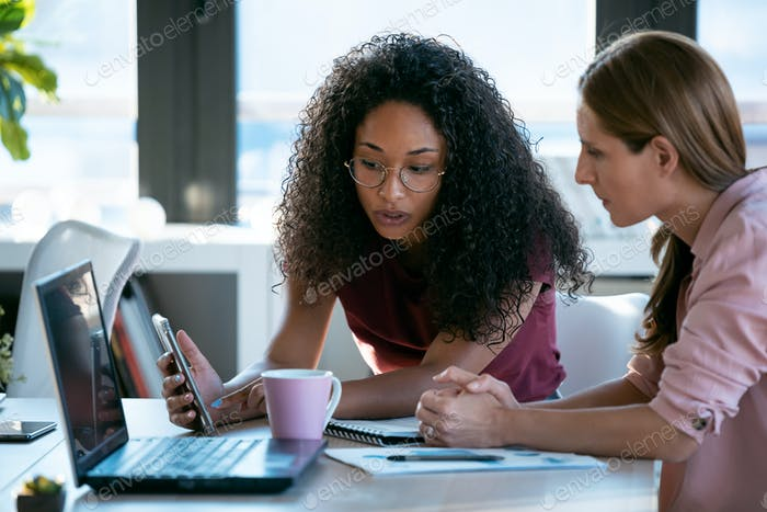Two beauty business women working together with laptop while talking about job news in the office.