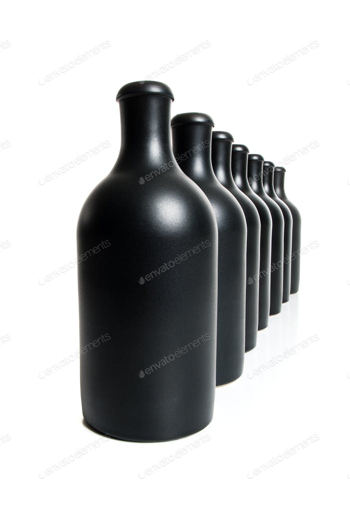 Set of several matte black bottles on a white background.