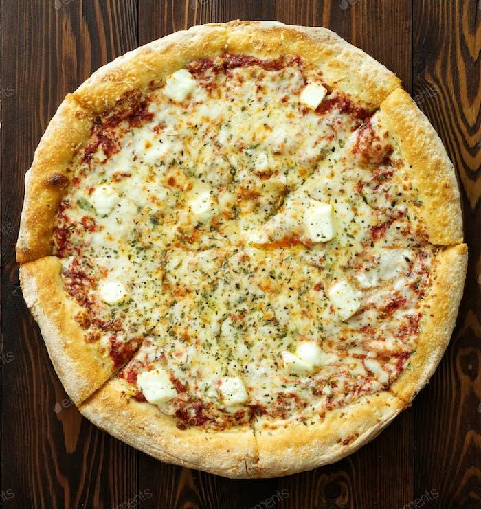 Four cheese pizza with Dor-blue, Parmesan, feta, oregano, mozzarella, tomato sauce, top view