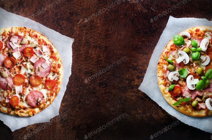 Two fresh italian pizzas with mushrooms, ham, tomatoes, cheese, olive, basil, on backing paper, dark