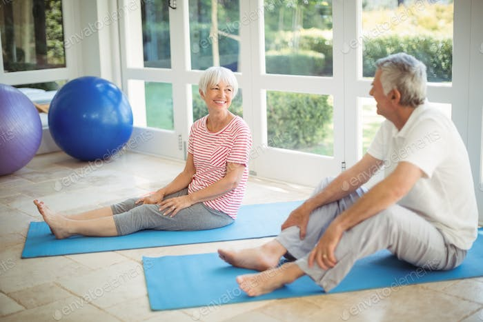 Happy senior couple interacting while performing exercise on exercise mat