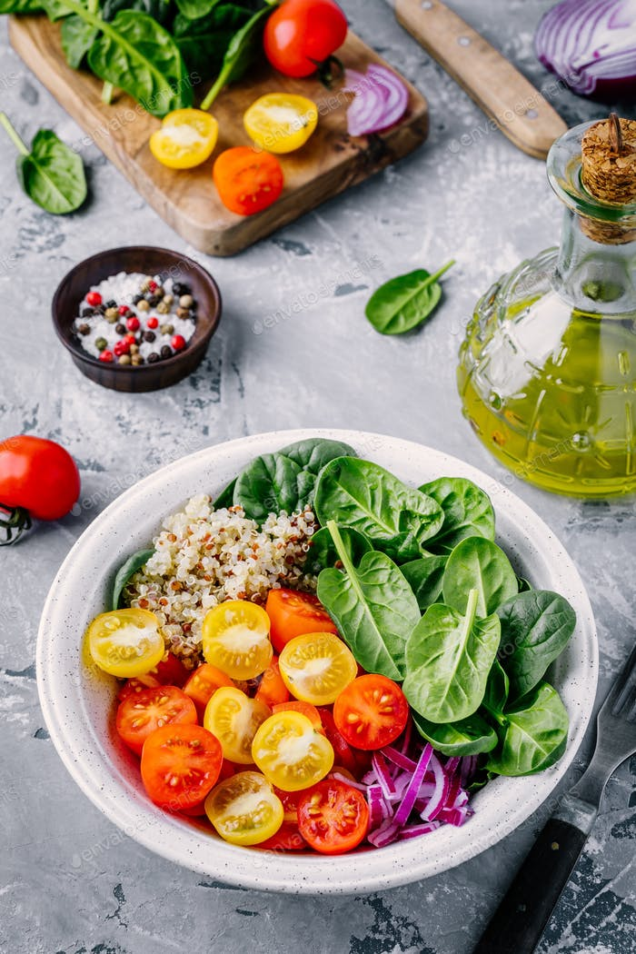 Healthy green bowl salad with spinach, quinoa, yellow and red tomatoes, onions and seeds