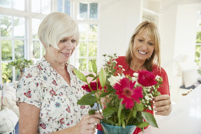 Senior woman and adult daughter arranging flowers at home