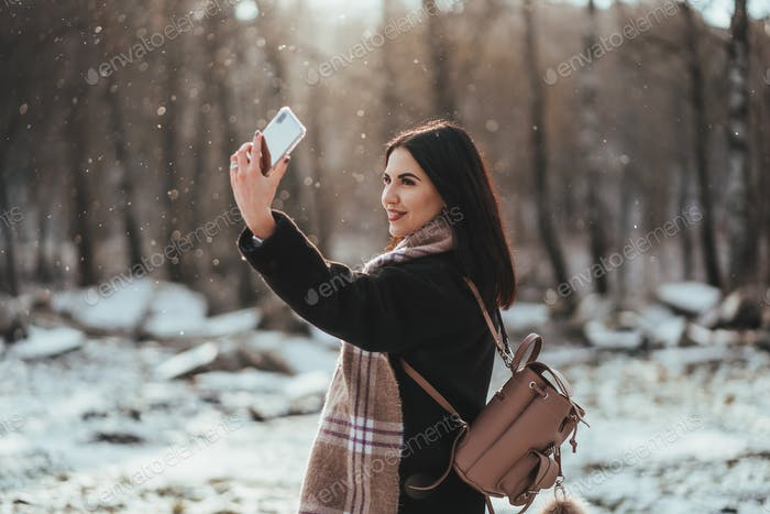 happy smiling teenage girl or young woman taking selfie by smartphone in winter park