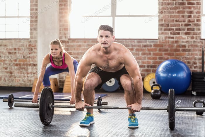 Two fit people working out in crossfit gym