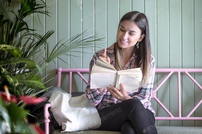 Junges Mädchen in einem karierten Hemd mit Öko-Tasche sitzt auf einer Bank im Laden und liest ein Buch