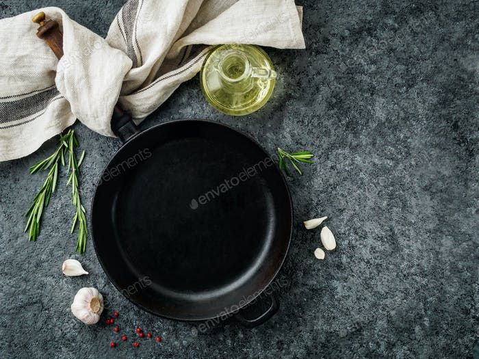 blank cast iron frying pan on dark grey concrete background, top view, blank space for text
