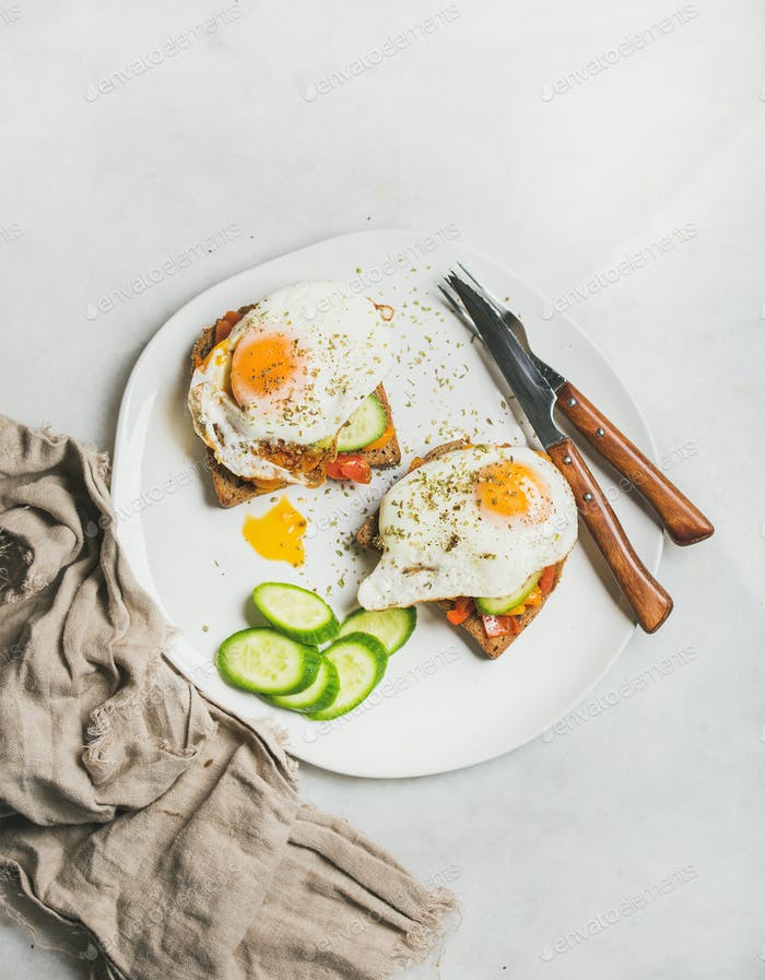 Breakfast toast with fried eggs, vegetables on white plate
