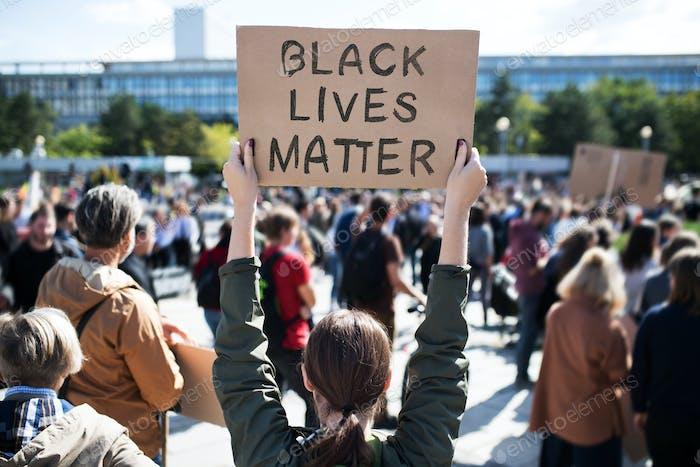 La vista trasera de las vidas negras importa a los manifestantes sosteniendo carteles y marchando al aire libre en las calles