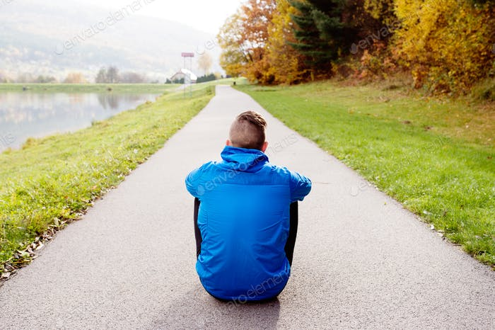Young runner in park sitting on asphalt path, rear view