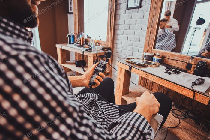 Young styilish man in checkered shirt is sitting at busy barbershop and holding trimmer for haircut