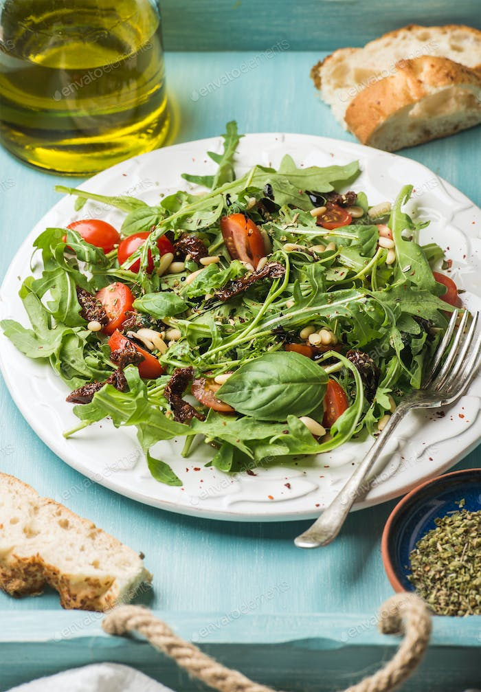 Salad with arugula, cherry tomatoes, pine nuts
