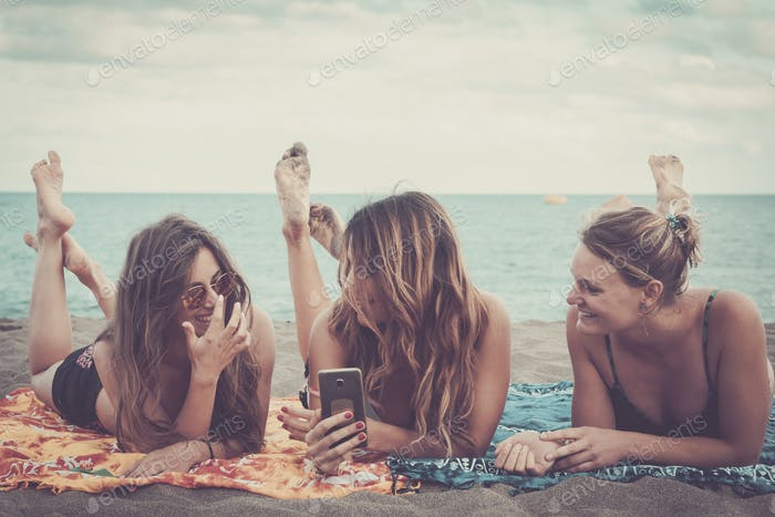 three nice girls use mobile phone technology to take pictures at the beach relaxing