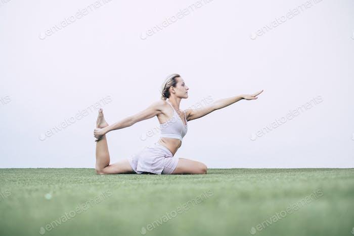schönes junges blondes Mädchen macht Pilates Yoga ausgeglichene Position
