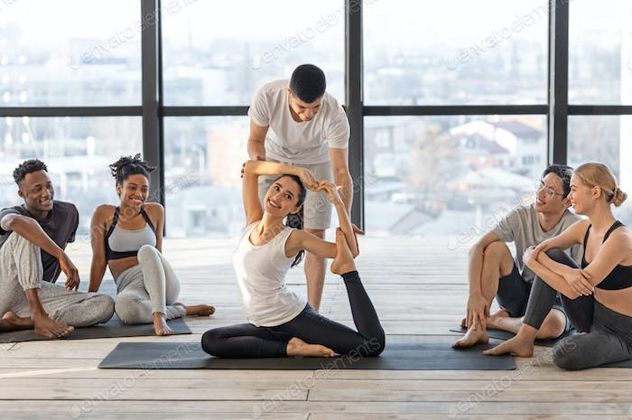 Professional yoga instructor helping to group member in difficult asana, correcting posture