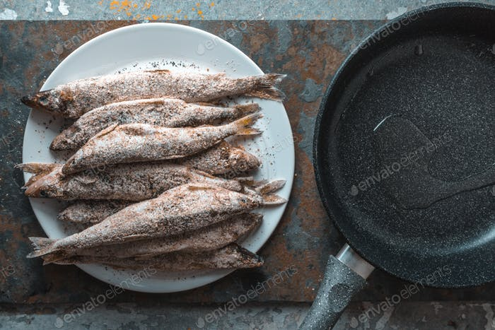 Fish on a plate, frying pan on a gray beige background