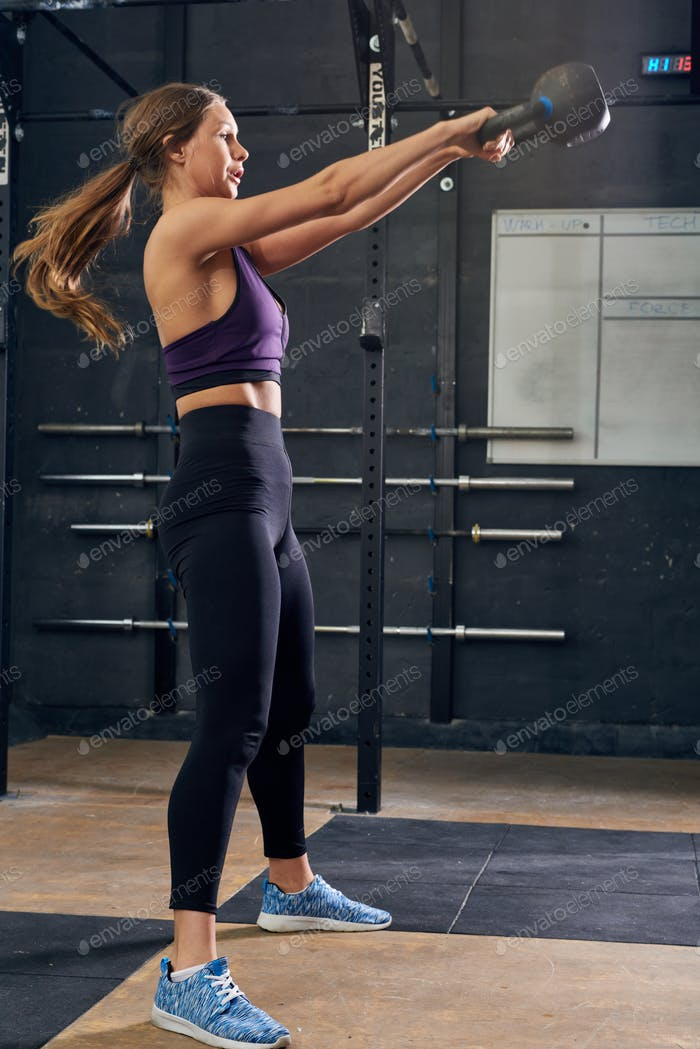 Young Woman Swinging Kettlebell in CrossFit Gym