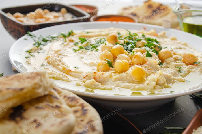 Closeup view at Hummus topped with beans olive oil and green coriander leaves