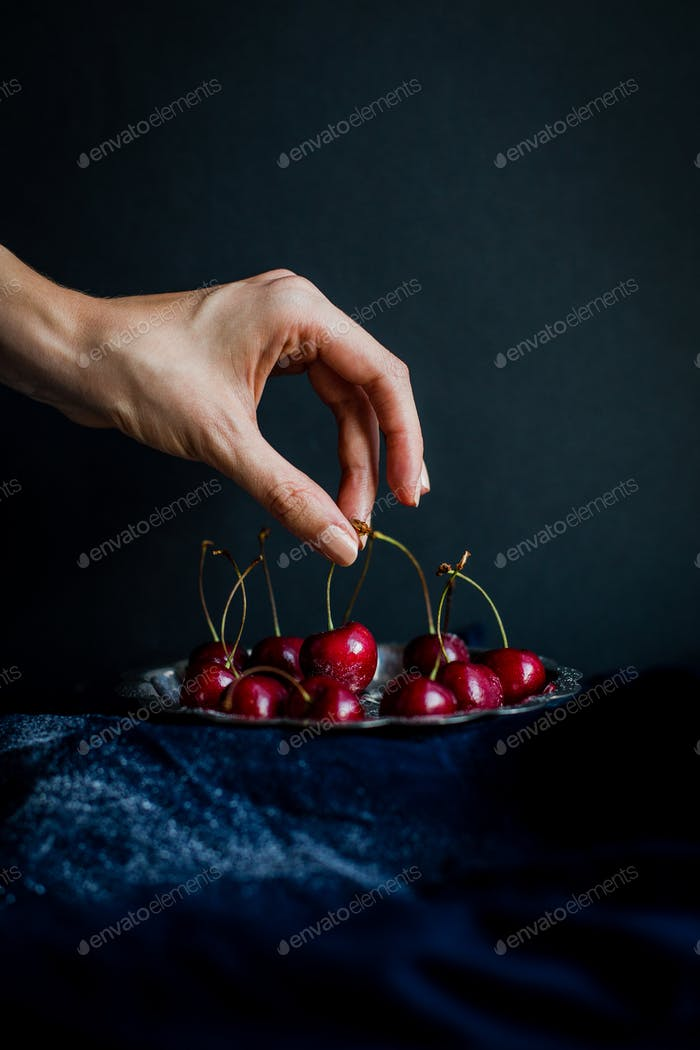 Hand Picking Red Cherries from Silver Platter against Black Background