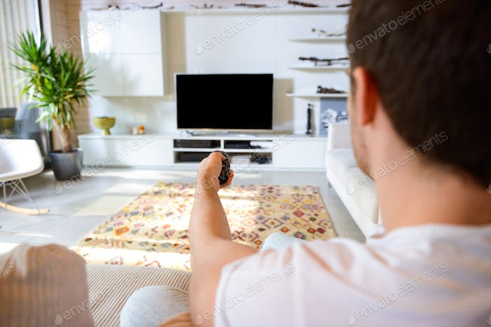 man sitting against tv