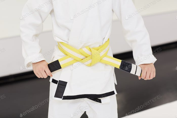 Boy tieing the yellow belt